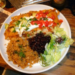 Vegetarian Black Bean Enchiladas Recipe - Flour tortillas are filled with creamy vegetarian refried black beans and baked with a homemade cilantro-salsa enchilada sauce in the veggie-packed dish.