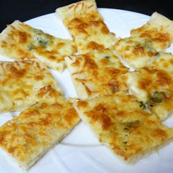 Garlic-Cheese Flat Bread Recipe - Perfect alongside soup or salad, this flat-bread uses refrigerated pizza dough as its base. This flat-bread also makes a great snack served with pasta sauce for dipping.
