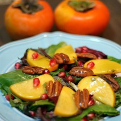 Persimmon and Pomegranate Salad Recipe - Sliced persimmons, pomegranate seeds, and toasted pecans are layered over herb salad mix and drizzled with a tarragon orange dressing for a delightful fall salad.
