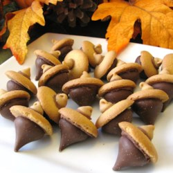 Acorn Candy Cookies Recipe - Chocolate kisses and vanilla wafer cookies make cute little acorns for decorating cakes and cupcakes. The nut of the acorn is a chocolate kiss, and the acorn's cap is a vanilla wafer with a butterscotch chip in the middle.