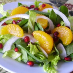 Pretty Pomegranate Salad Recipe - Super simple and delicious, this pomegranate, arugula, and spinach salad is a beautiful addition to any meal.