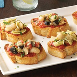 Contadina(R) Mediterranean White Bean Bruschetta Recipe - Slices of baguette are topped with pizza sauce and a chunky bean spread then topped with lemon zest and parsley for quick and tasty party appetizers.