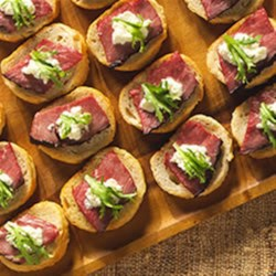 Crostini with Beef Tenderloin and Horseradish Recipe - Toasted bread rounds are topped with roast beef, zesty horseradish sauce, and curly frisee for a quick and delicious appetizer.