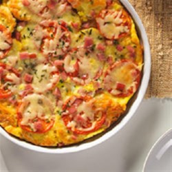 Ham and Cheese Egg Bake Recipe - Chopped deli ham and strips of cheese create layers of flavor in this baked egg casserole.