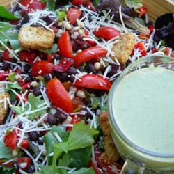 Cinco De Mayo Salad Recipe - Anchovy fillets are a surprisingly delicious addition to the spicy yogurt dressing in this mixed green salad with black beans, grape tomatoes, and fresh corn.