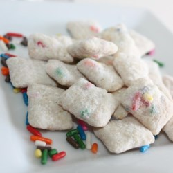 Confetti White Puppy Chow Recipe - A new twist on puppy chow includes white cake mix with sprinkles and vanilla almond bark for a festive, confetti white puppy chow.