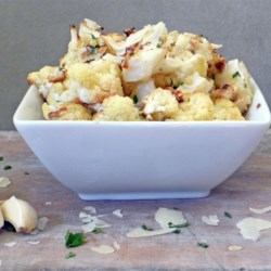 Roasted Garlic Cauliflower Recipe - Tender roasted cauliflower tossed in olive oil and garlic is topped with Parmesan and cheese and broiled until golden brown.
