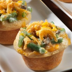 Mini Green Bean Casseroles Recipe - Here's a fabulous twist on a popular holiday casserole.  Refrigerated biscuits form the crusts that hold a classic mixture of green beans, cream of mushroom soup, milk, Cheddar cheese and French fried onions. It's a fun way to enjoy an all-time favorite dish.
