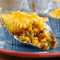 Mini Taco Tamale Pies Recipe - A beefy, cheesy filling is spooned into muffin-pan cups, topped with corn muffin mix and baked until golden brown. Give them a try--these tasty mini tamale pies will be a surefire hit at your dinner table.
