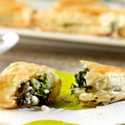 Campbell's Spinach and Feta Mini-Calzones Recipe - Feta cheese and spinach are wrapped in flaky puff pastry in this tasty appetizer. Good thing they're easy to make, because they're sure to disappear fast.