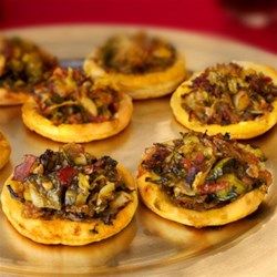 Caramelized Brussels Sprouts and Bacon Pizzettes Recipe - Braised Brussels sprouts, bacon and puff pastry combine to make these elegant and tasty appetizers that will steal the show at your next gathering.