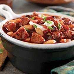 Smoky Pork, Bacon and White Bean Chili Recipe - This warm chili bowl made with white beans, crispy bacon and spiced pork tenderloin brings a savory twist to hearty comfort food.