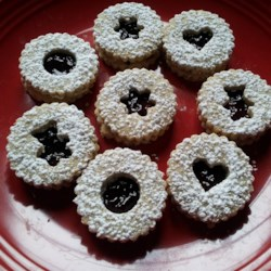 Raspberry Linzer Cookies Recipe - Raspberry jam is sandwiched between two sugar cookies and topped with a sprinkling of confectioners' sugar for a delightful cookie treat.