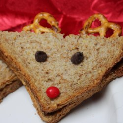 Reindeer Sandwiches Recipe - Transform a peanut butter sandwich into a reindeer sandwich using raisins, cherries, and pretzels as decorations for your favorite kids.