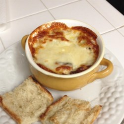Rich and Simple French Onion Soup Recipe and Video - A slice of French bread layered with three varieties of cheese is broiled on top of this decadent but simple french onion soup.