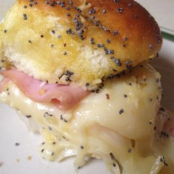 Baked Ham and Cheese Party Sandwiches Recipe - Mini rolls stuffed with deli ham and melted Swiss cheese are baked with a savory poppyseed-mustard sauce for an easy, tasty little bite or appetizer.