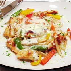 Restaurant-Style Chicken Scampi Recipe - Toss together tender chicken morsels with spaghetti, a rainbow of bell peppers, loads of garlic, a little onion and creamy Alfredo sauce, and you get Chicken Scampi right in your own home.