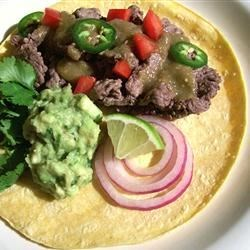 Carne Asada Tacos Recipe - You will love these easy and flavorful tacos! Strips of beef are marinated in lime and pepper, then quickly sauteed, and served in soft corn tortillas with tomatillo sauce and your favorite toppings!