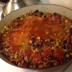 Chili With Turkey and Beans Recipe - Ground turkey, stewed tomatoes, and four kinds of beans make this chili quick, light, and flavorful. It's great served in bowls and sprinkled with cheese for a fall lunch or supper.