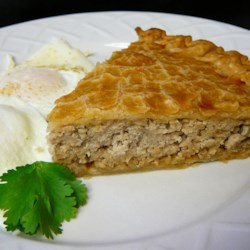 Meat Pie (Tourtiere) Recipe - Cinnamon, cloves and allspice are sprinkled over ground pork, mashed potato and onion and simmered in water for about an hour until the flavors are mingled and a thick sauce is created. This tasty filling is spooned into a deep dish pie crust, topped with another crust, and baked until deliciously brown.