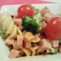 Ham Skroodle Salad Recipe - Smoked ham, crunchy broccoli, and slivers of fiery sweet red onions are tossed with pasta and a spicy mustard vinaigrette.