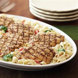 Alfredo Chicken and Broccoli Recipe - This quick weeknight dinner features grilled chicken breast fillets served over fettuccine in a creamy pesto Alfredo sauce with broccoli and roasted red peppers.