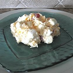 Ambrosia Fruit Salad Recipe - Shredded coconut and chunks of pineapple, mandarin oranges, marshmallows, pecans and fruit cocktail are folded into whipped topping and chilled.  Top with maraschino cherries when serving.