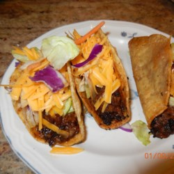 Beef Tacos Recipe - Hard shell tacos with ground beef simmered in ketchup; topped with Cheddar cheese, tomato and lettuce. For those who aren't crazy about spicy Tacos!