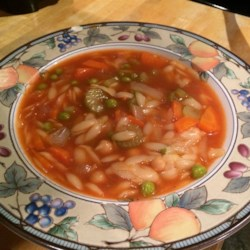 Tomato Orzo Soup Recipe - Rice-shaped orzo pasta, peas, diced carrots and celery are cooked in chicken broth in this soup which is finished with fresh minced parsley.