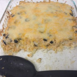 Rice With Olives And Green Chile Peppers Recipe - Rice is keeping pretty good company in this recipe--sliced black olives, diced green chili peppers and lots of shredded cheese. It's all layered and baked with sour cream until the cheese melts and the flavors have mingled beautifully.