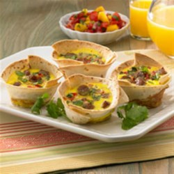 Breakfast Tortilla Cups Recipe - For those wanting a bit more spice to start the day, there's nothing better then perfectly portioned tasty tortilla cups!  These cups are packed with the wonderful flavors of eggs, cilantro, red bell pepper and Mexican cheese.  For the added kick, Johnsonville Hot & Spicy Breakfast Sausage Links are used to give you the needed heat to wake up your taste buds and get you going.  Serve with your favorite salsa for an added bonus to your morning fiesta.
