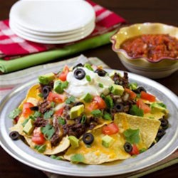Sweet and Spicy Beef Nachos Recipe - Beef roast is slow cooked in a sweet and spicy sauce, then shredded and piled on tortilla chips with shredded cheese and your favorite toppings for this hearty, crowd-pleasing snack.