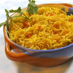 Apricot Almond Pilaf Recipe - Golden basmati rice studded with dried apricots and slivered almonds gets an exotic flavor from saffron and rose water in this company-worthy pilaf.