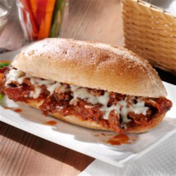 Italian Cheese Steak Sandwiches Recipe - Strips of chuck steak are browned then simmered in a spicy sauce. Serve on a hero roll and top with shredded mozzarella cheese.