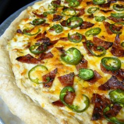 Jan's Jalapeno Popper Pizza Recipe - A cream cheese base replaces tomato sauce in this pizza topped with bacon and jalapeno peppers to bring poppers to pizza.