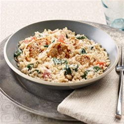 Creamy Rice, Chicken and Spinach Dinner Recipe - A hearty, flavorful skillet supper combines chicken breast strips flavored with Italian-inspired seasonings, quick-cooking brown rice, fresh tomatoes, and spinach. The dish is topped with Parmesan cheese before serving.