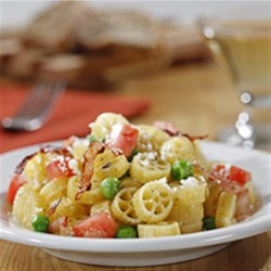 Mini Wheels with Peas, Ham and Tomato Recipe - Mini pasta wheels tossed with diced tomatoes, peas and ham are topped with grated cheese for this quick, kid-pleasing weeknight meal.