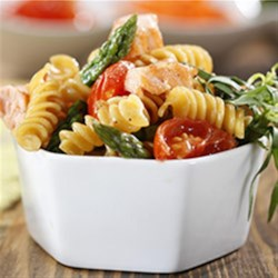 Rotini with Asparagus, Salmon and Cherry Tomatoes Recipe - Quickly browned chopped salmon is tossed with sauteed cherry tomatoes, scallions, and chopped fresh asparagus with rotini pasta in a lemony sauce.