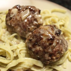 Swedish Meatballs (Svenska Kottbullar) Recipe and Video - Swedish meatballs made with ground beef and pork are gently spiced, baked, and served with brown sour cream gravy in this old family favorite recipe for Christmastime.