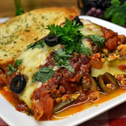 Zucchini Lasagna With Beef and Sausage Recipe - A lasagna made with layers of zucchini instead of noodles, a rich tomato meat sauce, and two Italian cheeses tastes like the lasagna you love.
