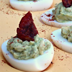 Little Green Eggs and Ham Devils Recipe - These little deviled eggs are filled with a spicy green avocado and egg yolk filling, and topped with paprika bacon.
