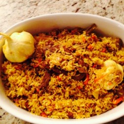 Uzbek Plov (Lamb and Rice Pilaf) Recipe - Spiced lamb is simmered with rice and whole heads of garlic in this Central Asia-inspired dish.
