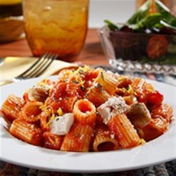 Mezzi Rigatoni with Chicken Thighs, Rosemary, Lemon Zest and Roasted Garlic Sauce Recipe - Cooked pasta is tossed with chunks of browned chicken in garlic tomato sauce with rosemary and lemon zest and topped with grated cheese.