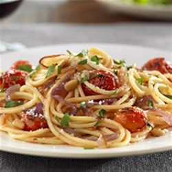 Gluten Free Spaghetti with Caramelized Red Onions and Whole Cherry Tomatoes, Pine Nuts and Pecorino Cheese Recipe - Roasted tomatoes and caramelized onions bring sweet-savory flavors to spaghetti tossed with grated cheese and toasted pine nuts.