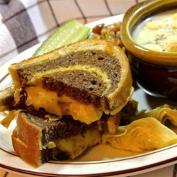 Gourmet Grilled Cheese Recipe - This gourmet grilled cheese layers sauteed onion, artichoke hearts, and smoked gouda between rye bread slices a fancy way to enjoy lunch.