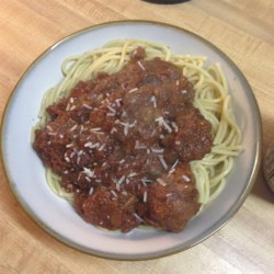 Megan's Amazing Spaghetti and Meatballs Recipe - Cheesy meatballs slowly simmered in a homemade tomato sauce served over a big plate of pasta makes for a comforting dinner with the family. Serve it with garlic bread to mop up all the sauce!