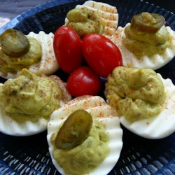 Avocado Deviled Eggs Recipe - Avocado deviled eggs topped with turkey bacon, jalapeno slices, and hot sauce are a colorful twist to the traditional recipe.