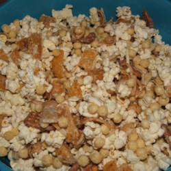 Lip-Smacking Popcorn Concoction Recipe - This is an easy and extremely tasty recipe! Every time I make this, I have people lined up to get the recipe! Cereal, corn chips, pretzels and nuts are coated with a vanilla confectioner's coating (also known as almond bark). This recipe makes a LOT--enough to fill an entire punch bowl and then some! Great for get-togethers.