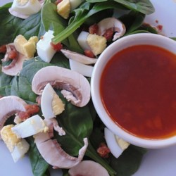 Wilted Spinach Salad and Bacon Vinaigrette Recipe - Spinach, mushrooms, and hard-boiled egg are tossed with a warm bacon vinaigrette creating a hearty and satisfying salad.