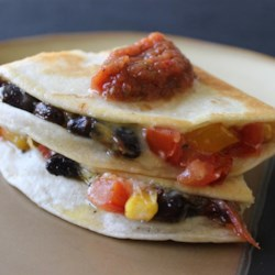 Bean Quesadillas Recipe and Video - Veggies, beans, and cheese sandwiched between two tortillas then heated in oil until golden on both sides.